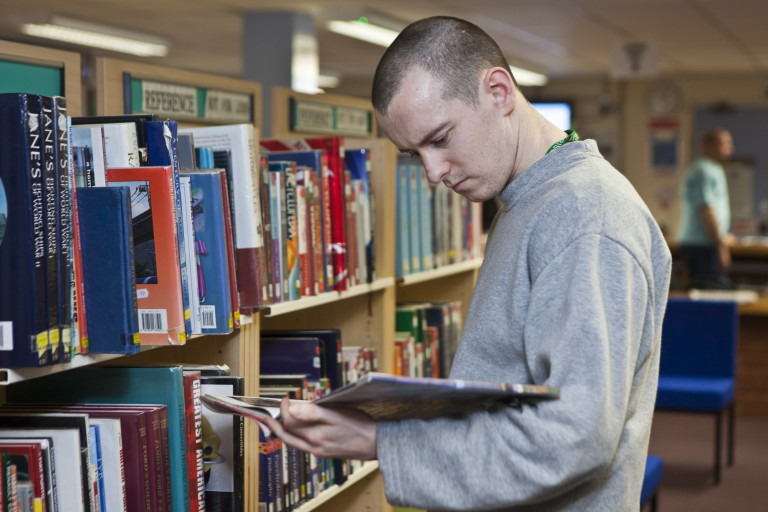 A prisoner reads a book in Featherstone prison library