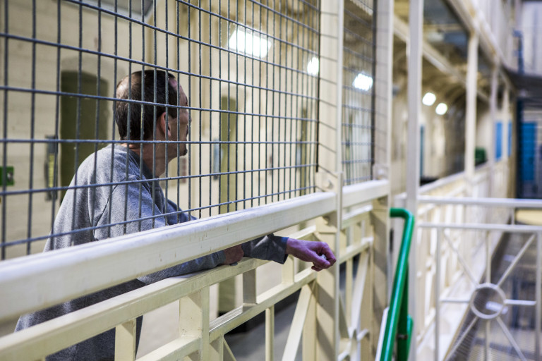 A prisoner leans against a barrier on a wing in Portland prison