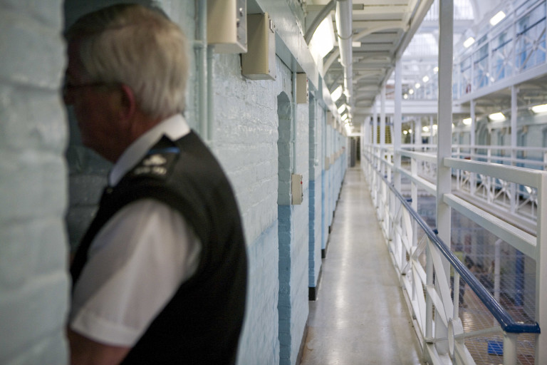 A prison officer looks into a cell in Wandsworth prison