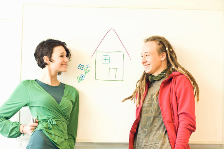 Two teenagers smiling at one another next to a drawing of a house