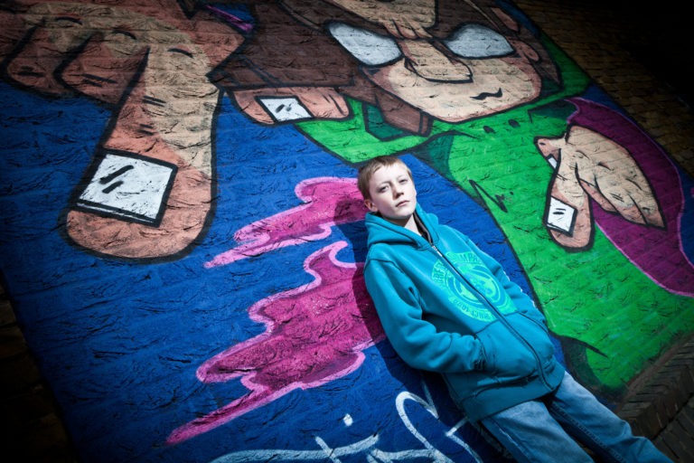 A teenage boy stands in front of graffiti